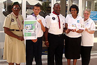 Cayman Islands Postal Service Philatelic Manager Karen McField presents a first-day cover to the Cayman Islands Scouts' Executive Commissioner Winston Hayle, and Assistant Chief Commissioner Elizabeth Scholefield. Cub Scout Leader Theloine Wellington and Assistant Patrol Leader Jasen Dawson (left) hold the Centenary of Scouting poster.