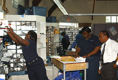 CIPS Deputy Postmaster General Anthony Williams (right) oversees British Virgin Islands staff training at the General Postal Office during a recent visit.